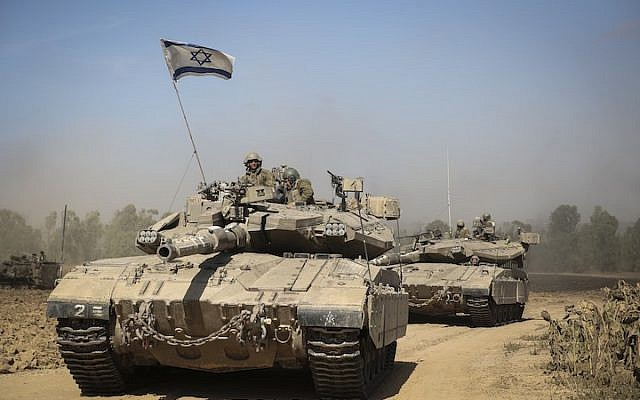 An Israeli tank crossing through a field in southern Israel near the border with Gaza, the day after Israel began its invasion of Gaza, July 18, 2014. (Hadas Parush/Flash 90/via JTA)