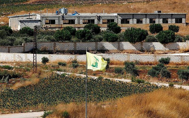 A photograph taken last week near the northern Israeli town of Avivim shows a Hezbollah flag in the Lebanon village of Aitaroun. A pro-Syrian Palestinian group accused Israel of carrying out a drone attack on one of its positions in Lebanon, hours after Hezbollah claimed it was targeted by a similar Israeli strike. Getty Images