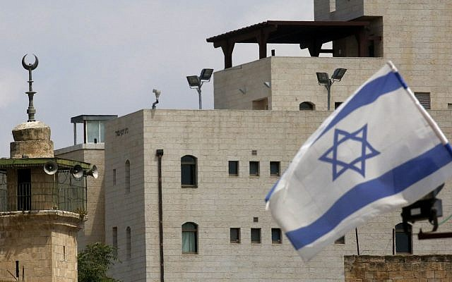 An Israeli flag is pictured near the minaret of a mosque at an Israeli settlement in Hebron, June 14, 2019. (Hazem Bader/AFP/Getty Images/via JTA)