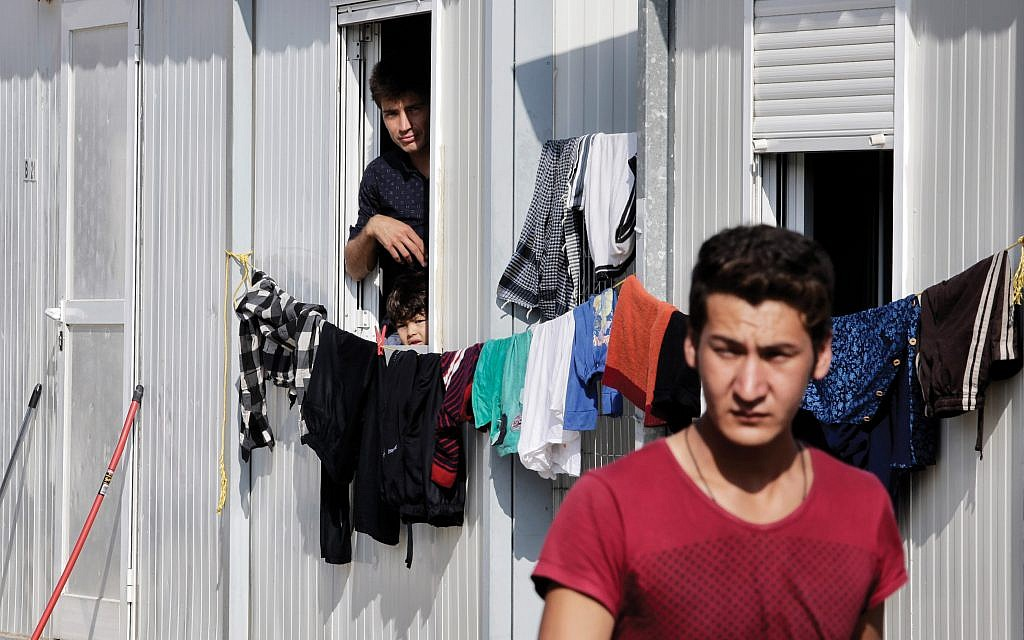 A refugee from Syria stands in front of his temporary housing in the Eleonas refugee camp in Greece. Getty Images