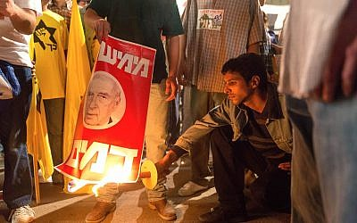 A still from 'Incitement' shows the Yehuda Nahari Halevi, whoe plays Yigal Amir, burning a poster of Yitzchak Rabin. Courtesy