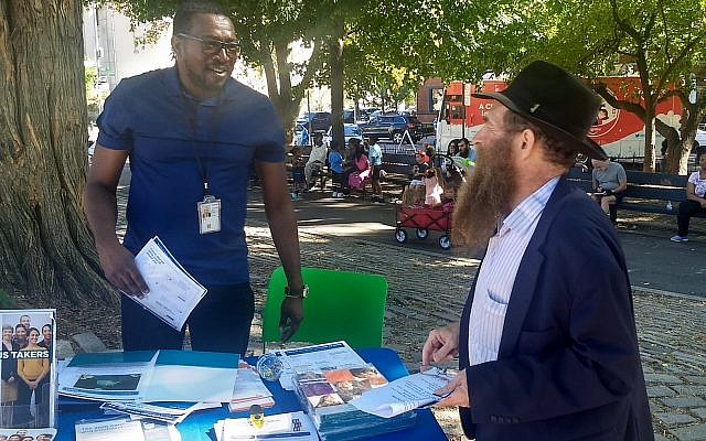 Rabbi Eli Cohen, right, the executive director of the Crown Heights Community Center, talks with a census volunteer at the #OneCrownHeights festival in Brooklyn, Sept. 15, 2019. (Ben Sales/JTA)