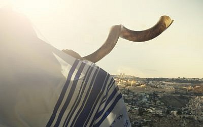 Illustrative photo: Jewish man blowing the Shofar with view of the holy city of Jerusalem