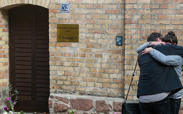 People mourn in front of the entrance to the Jewish synagogue on October 10, 2019 in Halle, Germany, Oct. 10, 2019, the day after a shooting attack there. (Jens Schlueter/Getty Images/via JTA)