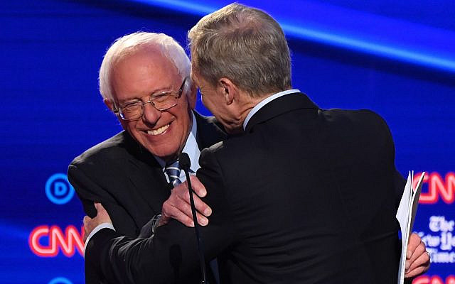Democratic presidential hopeful Vermont Senator Bernie Sanders,left, hugs businessman Tom Steyer during the fourth Democratic presidential primary debate at Otterbein University in Westerville, Ohio, Oct. 15, 2019. (Saul Loeb/AFP via Getty Images/via JTA)