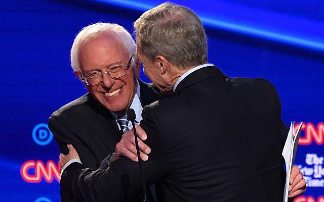 Democratic presidential hopeful Vermont Senator Bernie Sanders,left, hugs businessman Tom Steyer during the fourth Democratic presidential primary debate at Otterbein University in Westerville, Ohio, Oct. 15, 2019. (Saul Loeb/AFP via Getty Images/via JTA)