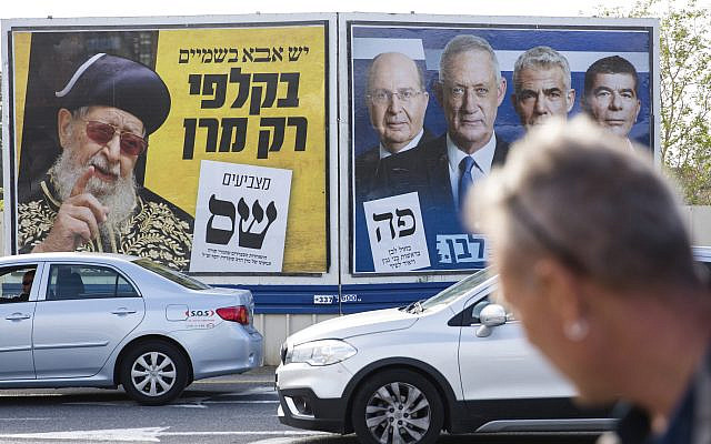 During the run-up to April's election, a man in Haedera looks at a Blue and White party election campaign poster showing its leaders Benny Gantz, Yair Lapid, Gaby Ashkenazi and Moshe Yaalon and Shas Party election campaign poster showing its spiritual leader Rabi Ovadia Yosef. Getty Images