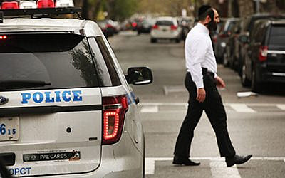 A chasidic man walks by a police car in an Orthodox Jewish neighborhood in Brooklyn. Getty Images