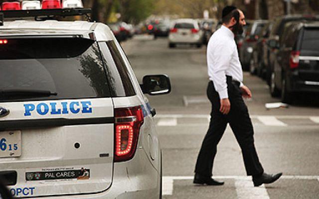A chasidic man walks by a police car in an Orthodox Jewish neighborhood in Brooklyn. Getty Images