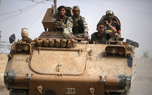 Turkish-backed Syrian fighters on the road near the border of Turkey. Turkey and its allies continue their assault on Kurdish-held border towns. Getty Images
