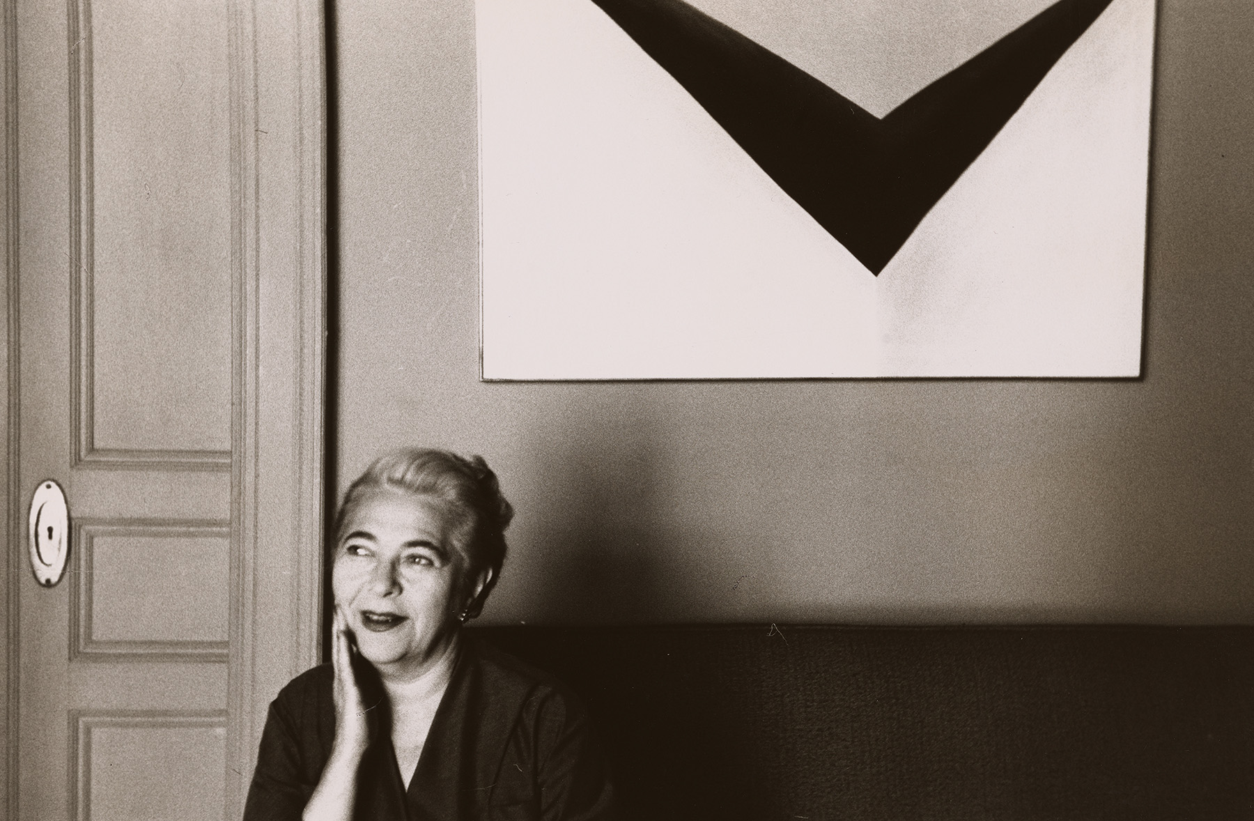 """Halpert posing with Georgia O'Keefe's """"In the Patio IX,"""" part of her personal collection. Archives of American Art, Smithsonian Institution/Downtown Gallery records"""