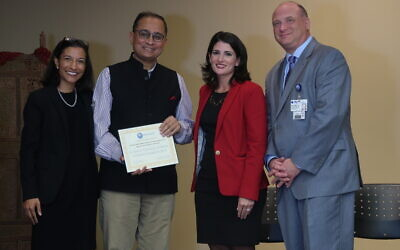 Sandeep Chakravorty, the Consul General of India, presents Parker Jewish Institute with a Proclamation in thanks of the center's support, devotion and compassion to the Indian community.  Standing with the Consul General are, from left, Dr. Shefali Shah, Tara Buonocore-Rut, Parker's  Executive Vice President – Corporate Strategy and Operations, and Michael N. Rosenblut, Parker's President and CEO.  Photo courtesy of Parker Jewish Institute