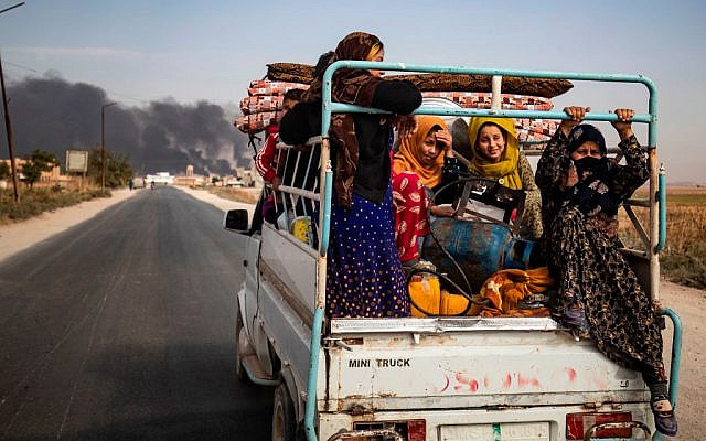 Displaced people, fleeing from the countryside of the Syrian Kurdish town of Ras al-Ain along the border with Turkey, ride in the back of a pickup truck along a road on the outskirts of the nearby town of Tal Tamr on October 16, 2019 as they flee a deadly cross-border Turkish offensive that has sparked an international outcry, with smoke plumes of tire fires billowing in the background to decrease visibility for Turkish warplanes in the area. Getty Images