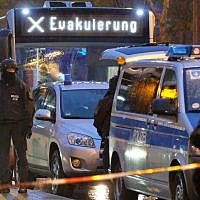 """A bus with the inscription """"evacuation"""" is escorted by police in Saxony-Anhalt, Halle in eastern Germany on October 9, 2019. Two people were killed in shots fired near a synagogue in Halle. JTA"""