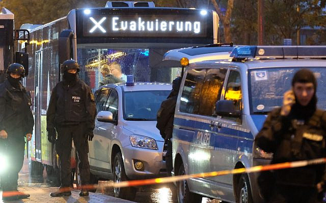 "A bus with the inscription ""evacuation"" is escorted by police in Saxony-Anhalt, Halle in eastern Germany on October 9, 2019. Two people were killed in shots fired near a synagogue in Halle. JTA"