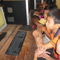 Arun Sothea runs an orphanage in Cambodia with the help of Jewish charities, Cambodian children learning on computers funded by Jewish Helping Hands. Courtesy of Arun Sothea / Charles Dunst