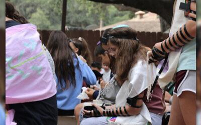 A photo of Hannah Landau during Shacharit (morning prayer service) at Camp Ramah in Ojai, wearing the tefillin that she made the previous summer at camp. Via Hannah Landau.