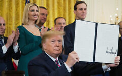 President Donald Trump shows the executive order he signed combatting anti-Semitism in the U. S. during a Hanukkah reception in the East Room of the White House Wednesday, Dec. 11, 2019, in Washington. (AP Photo/Manuel Balce Ceneta/via Times of Israel)