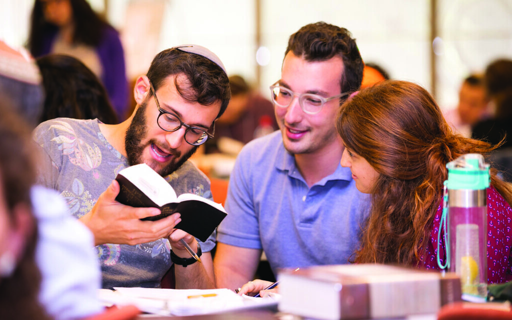 """Hadar students poring over texts. The institution's """"genuine commitment to halachic observance and egalitarianism"""" was a big draw for one student.  Courtesy of Hadar"""