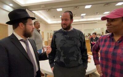 From left: Rabbi Moshe Schapiro, Chesky Deutsch and Pam Johnson talk during the charity drive. Courtesy of Benny Polatseck/JTA