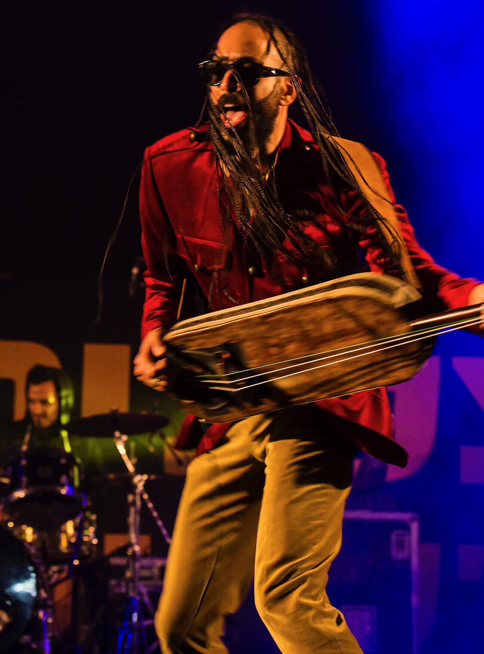 Ravid Kahalani of Yemen Blues plays the guembri on stage. Courtesy of Yemen Blues