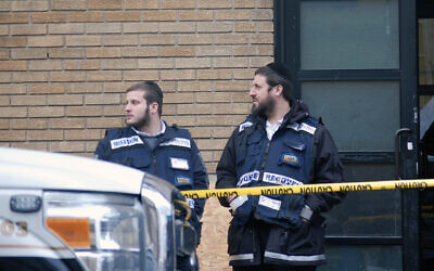 Chasidic members of Misaskim, which provides services for the care of the dead, stand in front of the K'hal Adas Greenville synagogue in Jersey City, N.J., next door to the JC Kosher Supermarket, the site of the deadly shooting that left three dead. Dec. 11, 2019. (Laura E. Adkins/JTA)