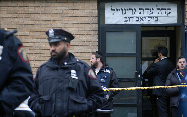 Chasidim, government officials and police officers stand in front of the K'hal Adas Greenville synagogue next door to JC Kosher Supermarket in Jersey City, N.J., the site of a deadly shooting, Dec. 11, 2019. (Laura E. Adkins/JTA)