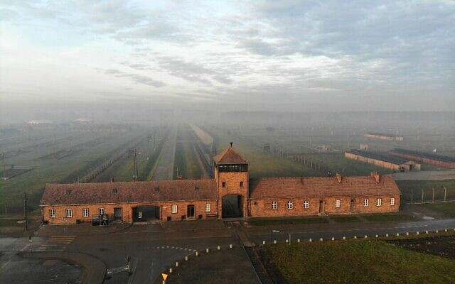This photograph taken on December 15, 2019, in Oswiecim, Poland, shows an aerial view of the railway entrance to former German Nazi death camp Auschwitz II - Birkenau with its SS guards tower. (Pablo GONZALEZ / AFP / via Times of Israel)