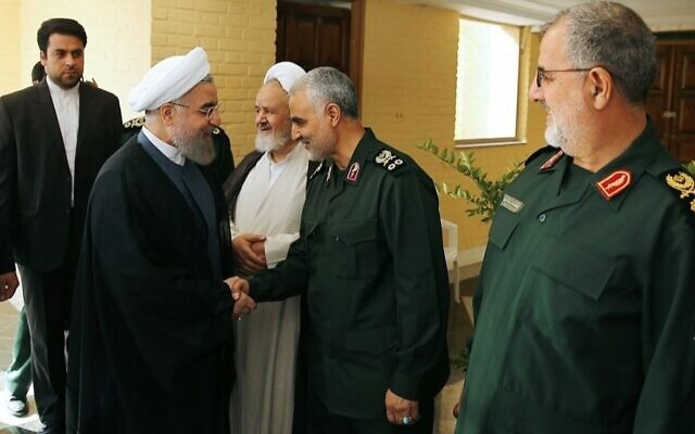 Iranian President Hassan Rouhani (L-2) shakes hands with Iranian Quds Force commander Qassem Soleimani (R-2) as Revolutionary Guards' ground forces commander Mohammad Pakpour (R) looks on during the 21st Nationwide Assembly of the Islamic Revolution Guards Corps (IRGC) Commanders in Tehran, Iran on September 15, 2015. JTA