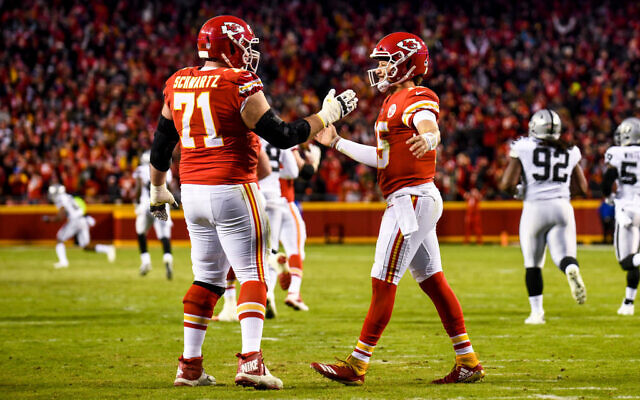 KANSAS CITY, MO - DECEMBER 30: Patrick Mahomes #15 of the Kansas City Chiefs is congratulated by teammate Mitchell Schwartz #71 after throwing his fiftieth touchdown of the season during the third quarter of the game against the Oakland Raiders at Arrowhead Stadium on December 30, 2018 in Kansas City, Missouri. (Photo by Jason Hanna/Getty Images)