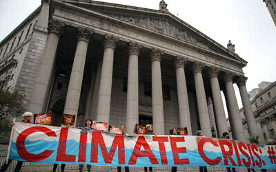 Environmental activists rally for accountability for fossil fuel companies outside of New York Supreme Court on October 22, 2019 in New York City. Tuesday is the first day of a trial where New York's attorney general is taking on ExxonMobil in a landmark case that accuses the oil corporation of misleading investors about the company's financial risks due to climate change. (Photo by Drew Angerer/Getty Images)