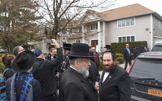 Members of Rabbi Chaim Rottenberg's community in Monsey, N.Y., gather in front of the house where five people were injured in a knife attack during a Hanukkah party. (Stephanie Keith/Getty Images/via JTA)