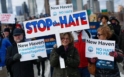 A woman holds a banner as she attends protests in support of the Jewish community called No Hate No Fear at the Brooklyn Bridge on January 5, 2020 in New York City. (Photo by Kena Betancur / AFP) (Photo by KENA BETANCUR/AFP via Getty Images)