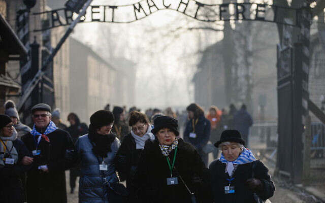Survivors of the Auschwitz concentration camp walk by the main gate bearing the motto Arbeit Macht Frei at the former Auschwitz I site on January 27, 2020 in Oswiecim, Poland. Photo by Omar Marques/Getty Images