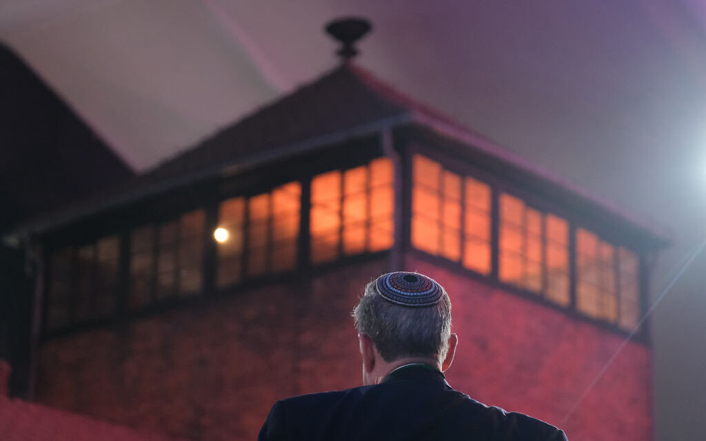 OSWIECIM, POLAND - JANUARY 27:  A man wearing a yarmulka stands next to the main tower at the entrance to the former Auschwitz-Birkenau concentration camp, which is covered under a large tent, prior to the official ceremony to mark the 75th anniversary of the liberation of the camp on January 27, 2020 near Oswiecim, Poland. International leaders as well as approximately 200 survivors and their families are gathering at Auschwitz today to attend the commemoration. The Nazis killed an estimated one million people at the camp during the World War II occupation of Poland by Nazi Germany. The Soviet Army liberated the camp on January 27, 1945.   (Photo by Sean Gallup/Getty Images)