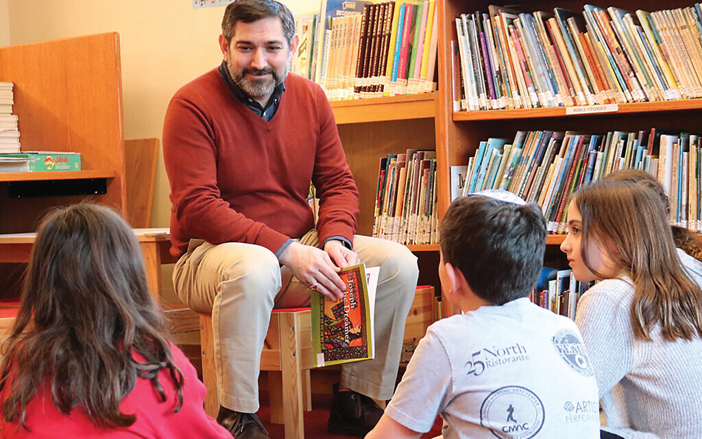 Westchester Jewish Center's senior rabbi, Jeffrey Arnowitz, discusses a book with fourth and fifth graders at the synagogue's Dan and Beverly Cannold Religious School. Courtesy of Westchester Jewish Center