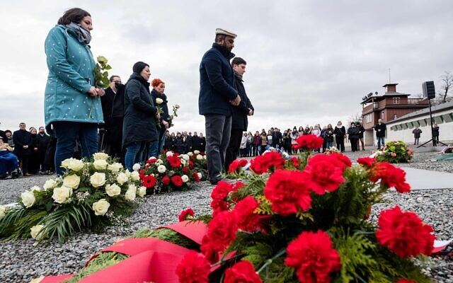 People lay flowers on a commemorative plaque during a ceremony at the memorial site of the former Nazi concentration camp Buchenwald near Weimar, eastern Germany, on January 27, 2020. JENS SCHLUETER/AFP via Getty Images