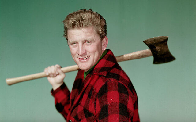 Portrait of American actor Kirk Douglas wearing a black and red checked jacket and holding an axe over his shoulder,  1950s. (Photo by Hulton Archive/Getty Images)