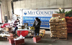 Metropolitan Council on Jewish Poverty workers packaging food in a Brooklyn warehouse for what has been a huge uptick in people needing food in the wake of the coronavirus outbreak. Courtesy of Met Council