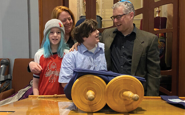 Minnesota nice! Spencer Snyder, center, reading from the Torah with his family on the bima. They distributed food meant for his bar mitzvah party to immune-compromised or sick people. Courtesy of the Snyders