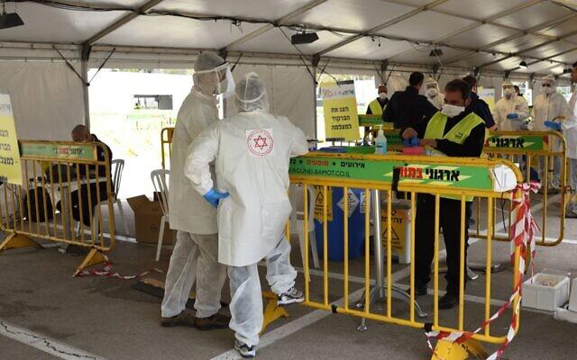 Magen David Adom medical team members, wearing protective gear, are seen at a drive-through site for coronavirus testing samples collection in Tel Aviv, March 20, 2020. (Gili Yaari/NurPhoto via Getty Images/via JTA)