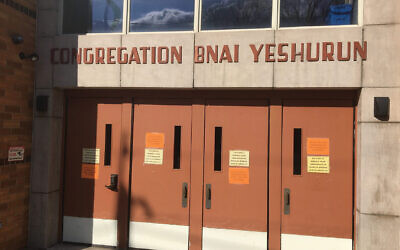 "The orange sign on the door of Congregation Bnai Yeshurun in Teaneck, N.Y., reads: ""As per the RCBC [Rabbinical Council of Bergen County] Bnai Yeshurun is closed."" JW Staff"