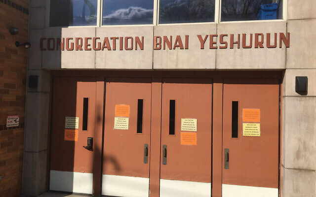 """The orange sign on the door of Congregation Bnai Yeshurun in Teaneck, N.Y., reads: """"As per the RCBC [Rabbinical Council of Bergen County] Bnai Yeshurun is closed."""" JW Staff"""