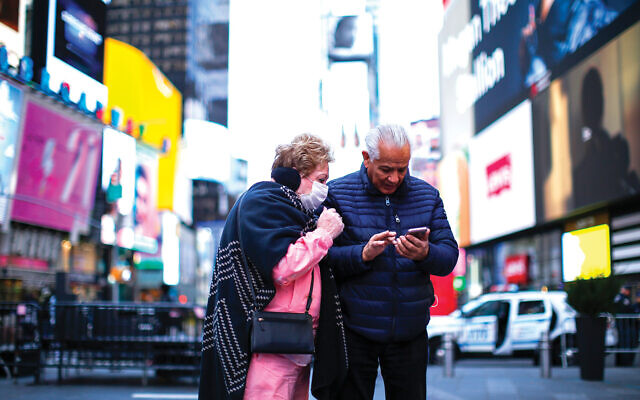 """Sign of the times: A woman dons a protective mask in Times Square. Jewish communal officials are especially concerned with seniors, who are particularly vulnerable to coronavirus and who are not coming to senior centers for lunches and socializing. """"We have seen a tremendous drop in clientele,"""" says a UJA-Federation of New York official. Getty Images"""