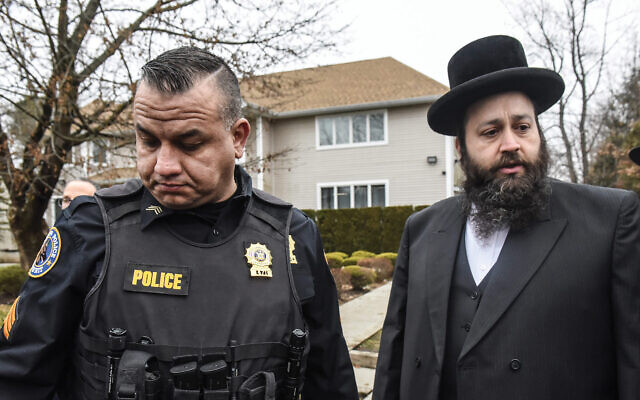 A member of the Ramapo police stands guard in front of the house of Rabbi Chaim Rottenberg last December in Monsey. Five people were injured in a knife attack during a Chanukah party. Stephanie Keith/Getty Images