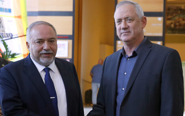 Avigdor Lieberman, left, and Benny Gantz shake hands after a private meeting in the central Israeli city of Ramat Gan, March 9, 2020. (Jack Guez/AFP via Getty Images/via JTA)