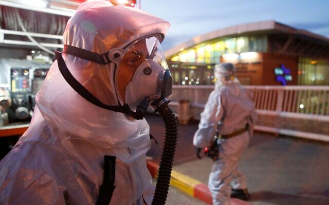 """A firefighter looks on before spraying disinfectant at the Moshe Dayan Railway Station in Israel's central city of Rishon Letzion near Tel Aviv on March 22, 2020, after Israel barred residents from leaving home for """"non-essential"""" reasons and stopped night-time public transport, tightening already strict measures to fight the spread of coronavirus. JACK GUEZ/AFP via Getty Images"""