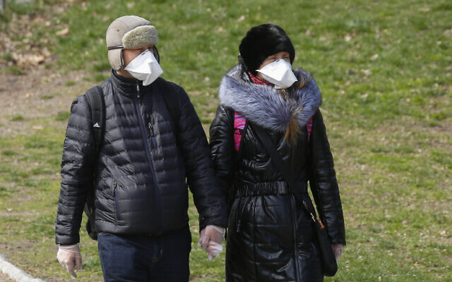 A couple wears face masks and surgical gloves as they walk in Central Park on March 22, 2020 in New York City. Kena Betancur / AFP via Getty Images