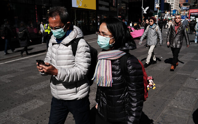 People walk through Manhattan with surgical masks as fears of the coronavirus spreading through the U.S. increase on March 04, 2020 in New York City. Travel, business, schools and other aspects of American life are beginning to be affected by the virus as new cases emerge. Spencer Platt/Getty Images