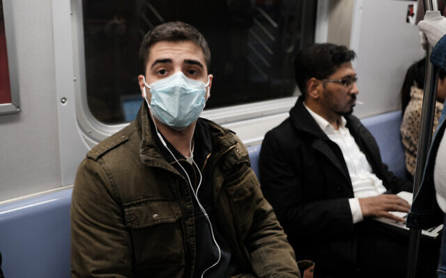 A man wears a medical mask on the subway as New York City confronts the coronavirus outbreak on March 11, 2020 in New York City. Spencer Platt/Getty Images